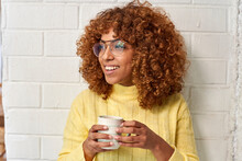 Woman With Coffee Cup Contemplating Against Brick Wall