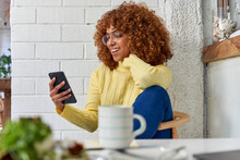 Happy Female Entrepreneur With Coffee Cup Checking Mobile Phone In Cafe