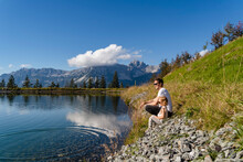 Father Sitting With Little Daughter On Shore Of Alpine Lake
