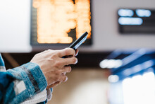 Close-up Of Man Using Mobile Phone While Standing At Subway Station