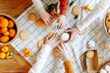 Hands Of Siblings Taking Cookies And Oranges On Table At Home