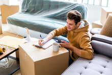 Smiling Man With Mobile Phone Writing On Paper Over Cardboard Box In New Home