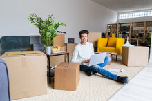 Smiling Young Man With Laptop Sitting In Messy Living Room At New Apartment