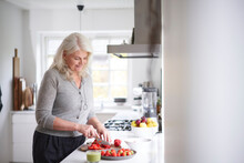 Retired Woman Cutting Strawberries On Board In Kitchen At Home