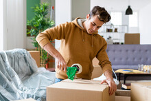 Young Man Applying Adhesive Tape On Cardboard Box While Moving In New Home