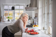 Thoughtful Retired Woman Leaning On Kitchen Counter With Strawberries In Apartment