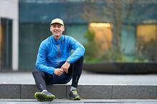 Smiling Mature Man Wearing Cap While Sitting On Pathway