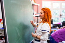 Young Female Nurse Looking At Blackboard In Rehabilitation Center