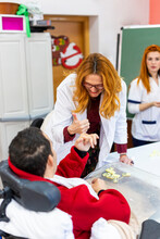 Smiling Female Caregiver Doing Thumbs Up Gesture With Disabled Man In Nursing Home