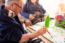 Mature Disabled Man Painting Twig At Rehabilitation Center