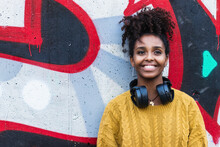 Smiling Young Woman With Headphones Standing Against Graffiti Wall