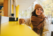 Smiling Young Woman With Disposable Coffee Cup Looking Away At Street Cafe During Winter