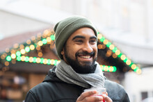 Close-up Of Cheerful Bearded Man Holding Drink Looking Away Against Illuminated Christmas Lights