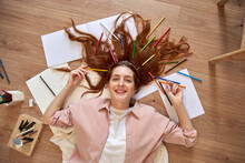 Smiling Female Artist With Bunch Of Colored Pencils In Hair While Lying Down At Home