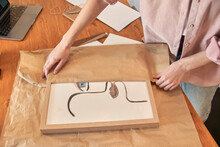 Female Freelancer Preparing Package In Brown Paper While Working At Home