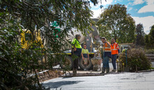 Four Men In Hi-vis Working To Make A Concrete Driveway