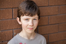 Portrait Of A Nine Year Old Boy Standing Against Brick Wall