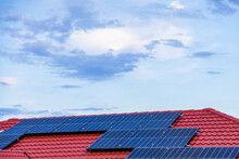 Solar Panels On Red Tiled Roof Of Home