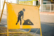 Yellow Digging Road Work Sign Near Construction Site On Footpath