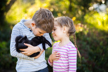 Two Children Cuddling With Pet Rabbit Outside