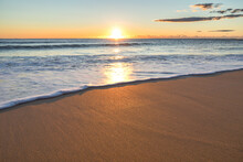 The Sun Rises Over Collaroy Beach Reflecting On Water And Sand