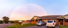 Brightly Coloured Rainbow Curtain Over Houses At Dusk