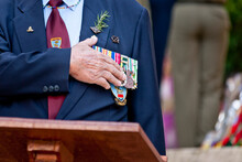 Veteran With His Hand On His Heart And Medals During An Anzac Service