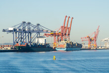 Cargo Ships Lined Up Under Cranes At A Sea Port