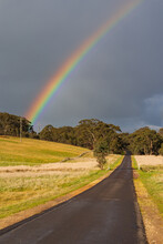 A Rainbow In A Dark Sky Over A Wet Country Road