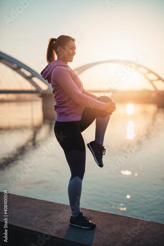 Fototapeta Happy female jogger standing and enjoying in beautiful river sunrise