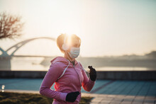 Beautiful Young And Fit Woman In Good Shape Is Running And Jogging Alone On City Bridge Street. She Is Wearing Protective Face Mask To Protect Herself From Virus Or Allergy Infection.