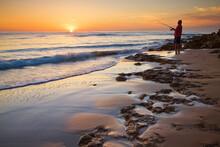 A Fisherman On The Coast At Sunrise