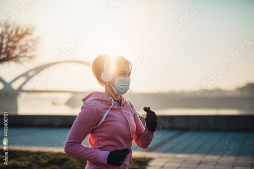 Obraz Beautiful young and fit woman in good shape is running and jogging alone on city bridge street. She is wearing protective face mask to protect herself from virus or allergy infection.  - fototapety do salonu