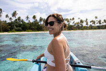 Woman Looking Back Over Her Shoulder On A Kayak Near A Tropical Island Beach