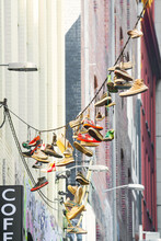 A Collection Of Footwear Hanging In A City Laneway