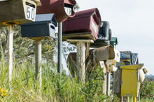Looking Up At A Row Of Colourful Letterboxes On Posts