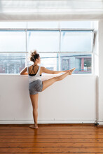 Ballet Dancer Stretching And Pointing Toes On A Ledge In A Studio