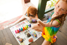 Two Girls Painting Rocks On A Verandah