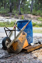 Orange Wheelbarrow And Blue Barrel On Wooden Pallet