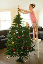Girls Decorating A Christmas Tree