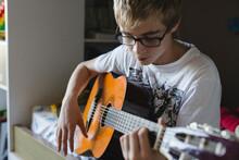 Teenage Boy Playing Guitar In His Bedroom