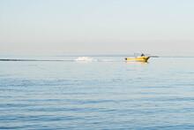 Yellow Fishing Boat Cruising Along The Calm  Blue Bay