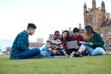 Group Of Young University Students Hanging Out Sitting On Grass Studying And Using Devices