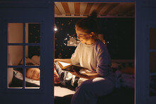 Mother Reading Book To Sleeping Daughter