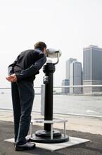USA, New York City, Manhattan, Man Looking At Skyline Through Telescope