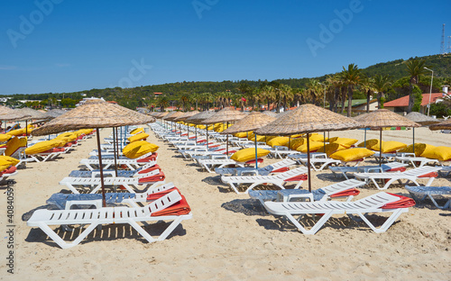 Tela Empty sunbeds and parasols on morning, by the sea