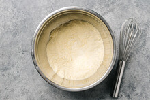 Cornmeal Mix In A Stainless Steel Bowl With A Wire Whisk