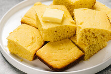 Plate Of Golden Cornbread Squares With Butter