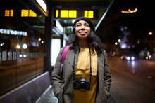 Woman Standing With A Camera Waiting At The Bus Station At Night