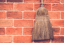 Old Broom Hanging On Red Brick Wall Background. Retro Filter